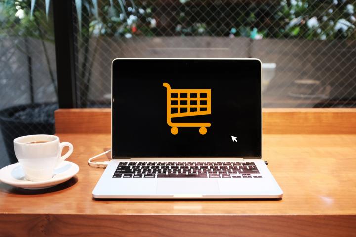 Kaffeetasse, aufgeklappter Laptop mit Einkaufswagen-Symbol