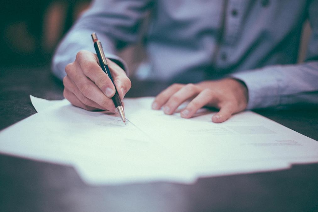 Hände, die mit einem Kugelschreiber schreiben